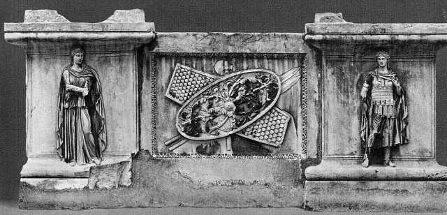 Trofeo con armi barbariche (scudi, lance e un'ascia), posto fra le personificazioni di due province romane. Rilievo su plinto, marmo, II sec. d.C. dall'Hadrianeum. Roma, P.zzo dei Conservatori.